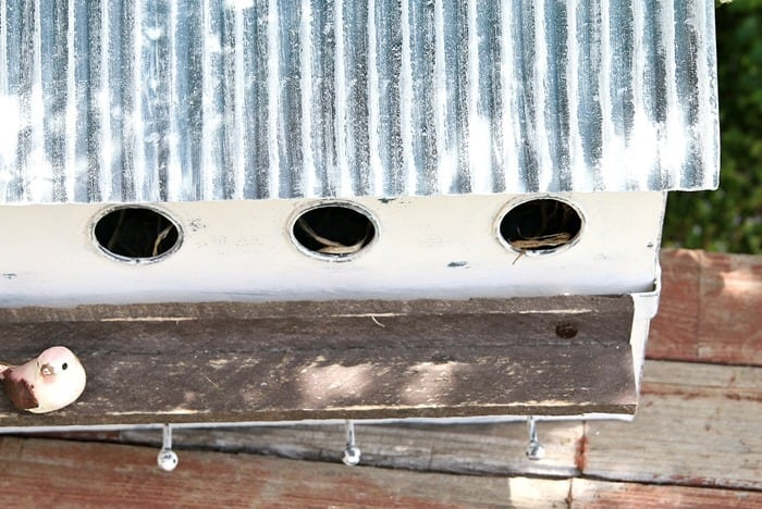 multi hole condo birdhouse painted white with a tin roof