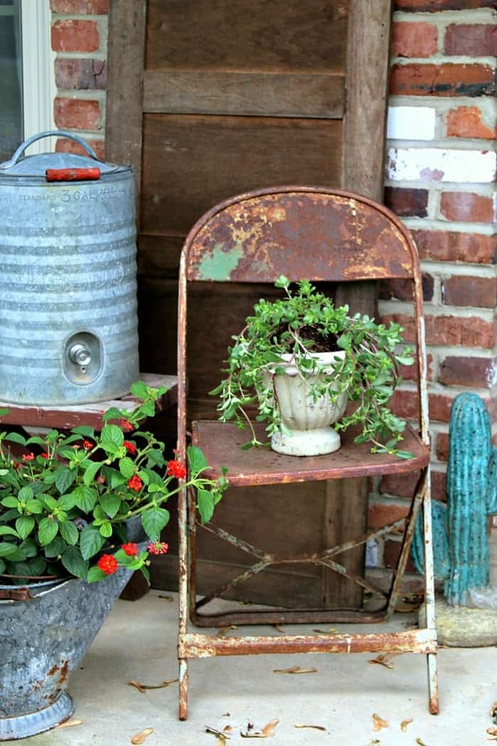Porch flowers in rusty pots and rusty chairs