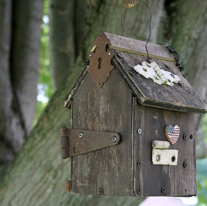 old wood birdhouse decorated with rusty hinges and jewelry