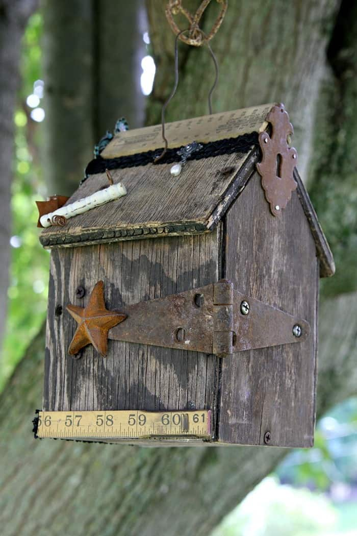 rusty star and hinge decorate a weathered birdhouse