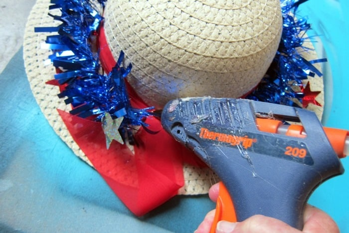 use hot glue to adhere sparkle garland to the hat