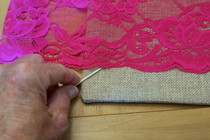 use hot glue to adhere lace and ribbon to crafts