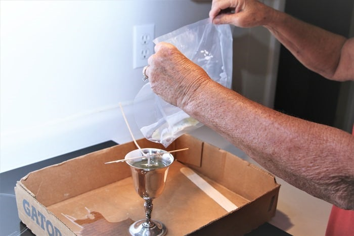 make a candle by pouring melter wax into container with wick