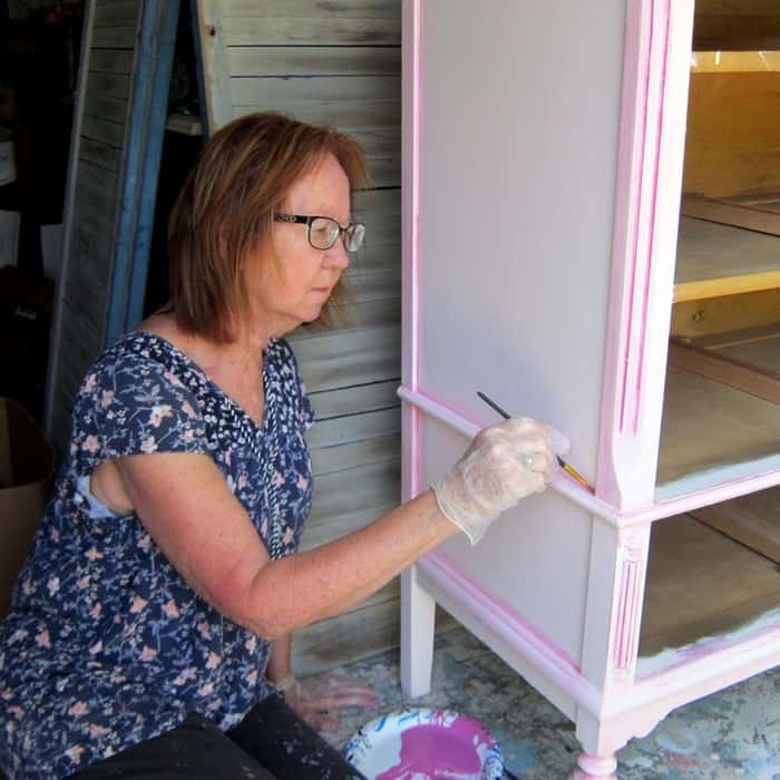 Kathy Owen creator at Petticoat Junktion painting furniture with custom mix paint