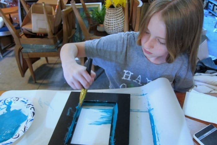 Sofi painting a picture frame