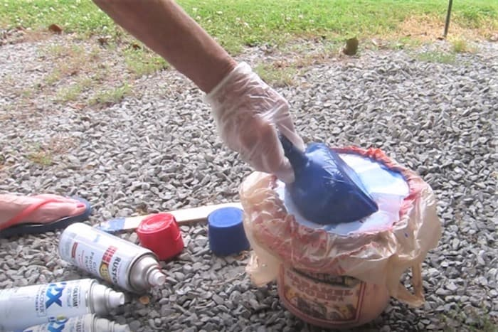 dipping a recycled bottle into water and spray paint hydro dip spray paint project (2)
