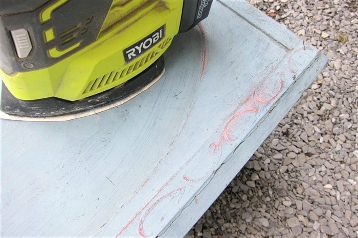 sanding paint with a battery sander