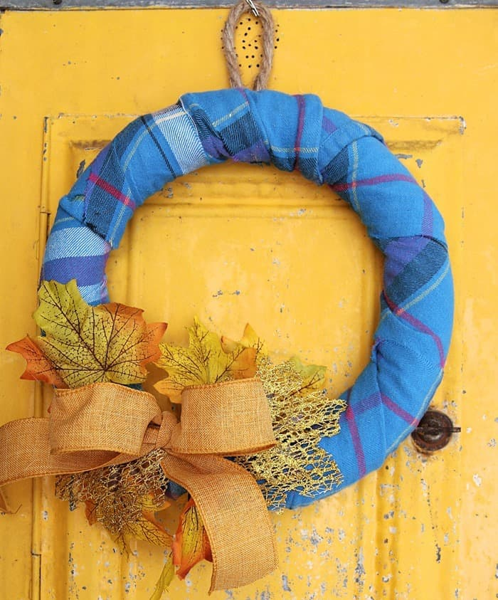 wreath form wrapped with Flannel and decorated with Fall leaves and a bow