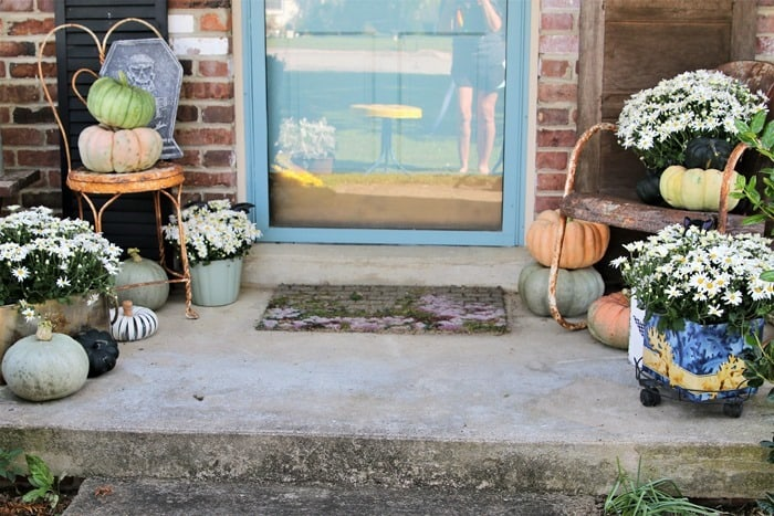 Porch decorations with mums, pumpkins, and rusty chairs